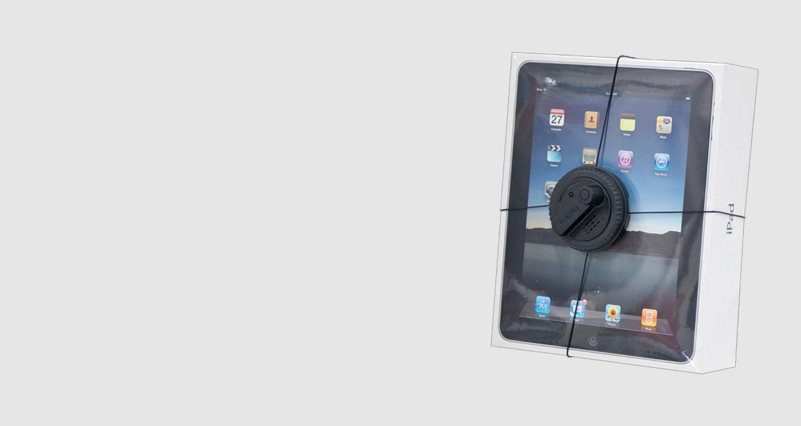 Une tablette iPad dans son emballage entouré d'un système antivol de type araignée